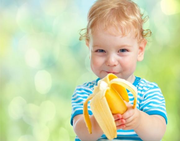 happy kid eating banana fruit